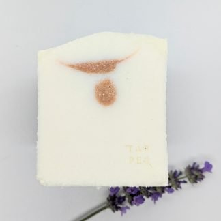 white cuboid bar of soap with a small pink dot and line swirl