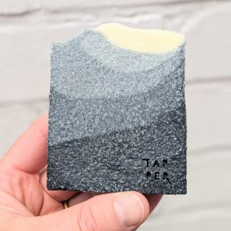 cuboid bar of soap. Ombre black to light orange in colour.