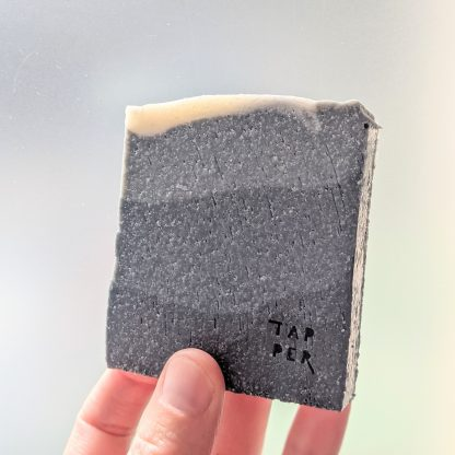 cuboid bar of soap. black to grey in colour with some small green swirls on top.