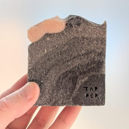 cuboid bar of soap. black to grey with a pink blob on top. stone like in texture.