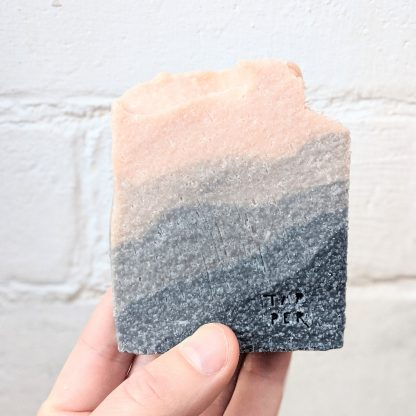 cuboid bar of soap with a graduated colour gradient from dark grey to pink. Peaks on one edge.